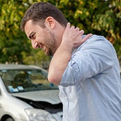 Man rubbing back of neck after car accident