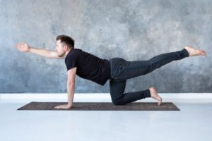 man doing Bird Dog for back pain after a car accident in Dallas